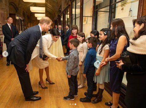 笑顔で少年と握手するメーガン妃。